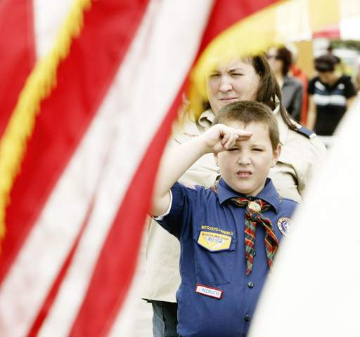 Cub Scout Pack 355 member John Prusko salutes during the National Anthem sung by Paula Szum during Glendale Heights International Day festival at Camera Park Sunday in Glendale Heights.