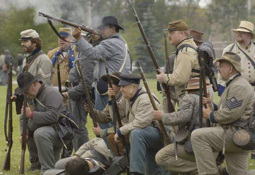 Confederate troops fire on Union positions in a battle re-enactment during Civil War Days at Lehmann Mansion Sunday in Lake Villa.