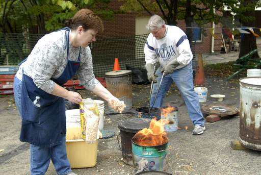 Tim Pfiffner and Cindy Wilkins work together in demonstrating the process of Raku pottery Sunday during pottery day at Blackberry Farm in Aurora.