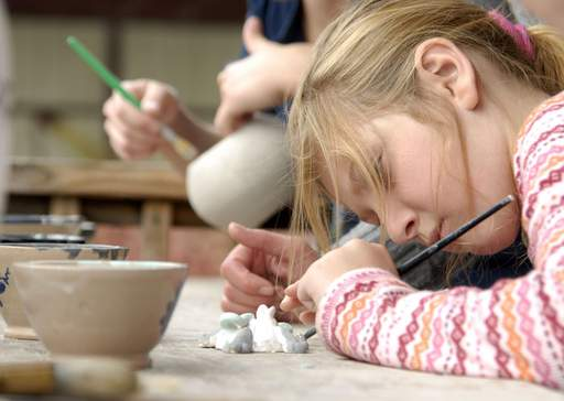 Fiona Keane, 9, of Aurora focuses on painting her custom pottery at Blackberry Farm Sunday morning.