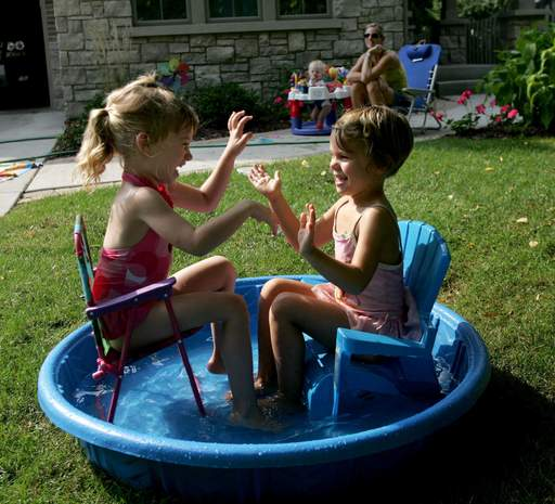 Korky Cunningham looks on with her one-year-old son Sullivan as her daughter Kaylie Cunningham, 4, left, has a playdate with her friend Sara Scornavacco, right, at Kaylie's home in Wheaton on Tuesday. They were able to play around in the pool due to the unseasonably-warm temperatures.