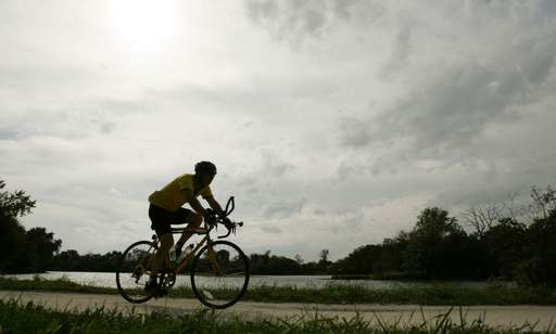 Les Eastwood of Barrington Hills pedals north on the Prairie Trail near the Fox River Thursday afternoon in Carpentersville. Near-record warm temperatures provided an unusual twist on the first full day of autumn in the Fox Valley.